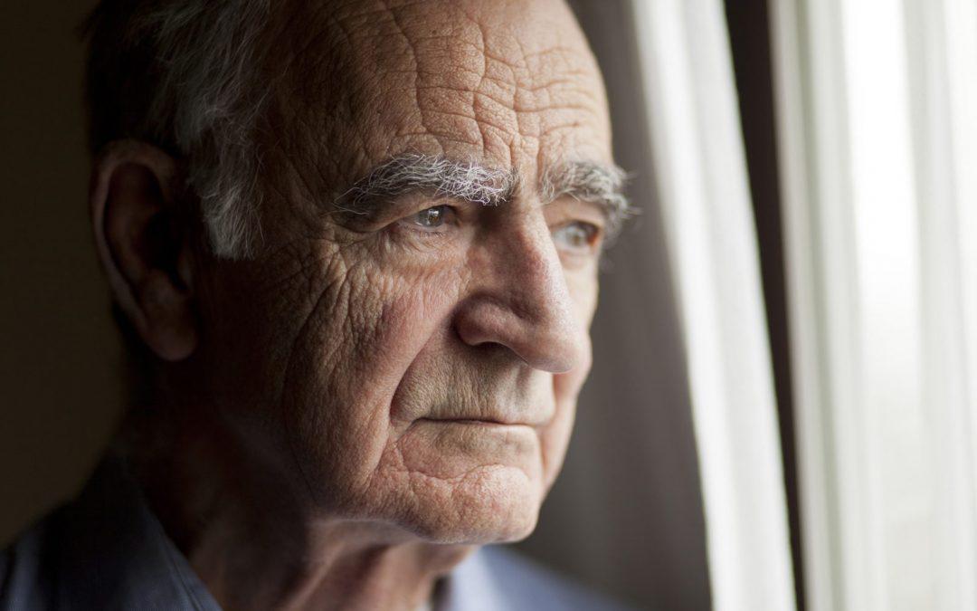 signore anziano che osserva dalla finestra