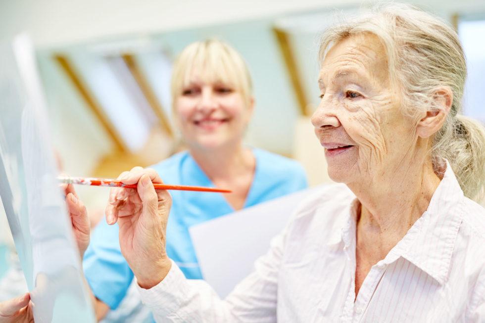 signora anziana dipinge con infermiera