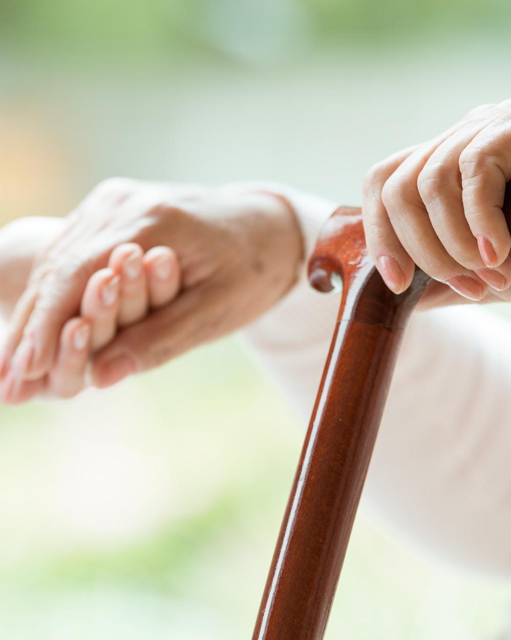 assistenza a signora anziana con bastone