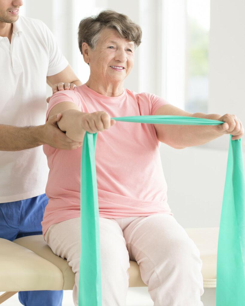 riabilitazione a signora anziana con elastici