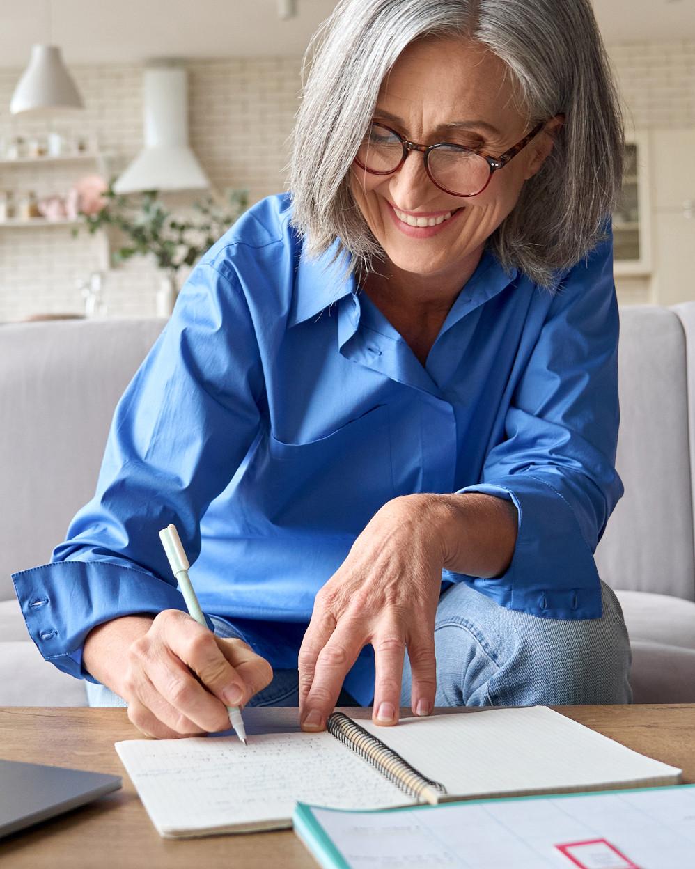 signora anziana che scrive su un bloc-notes