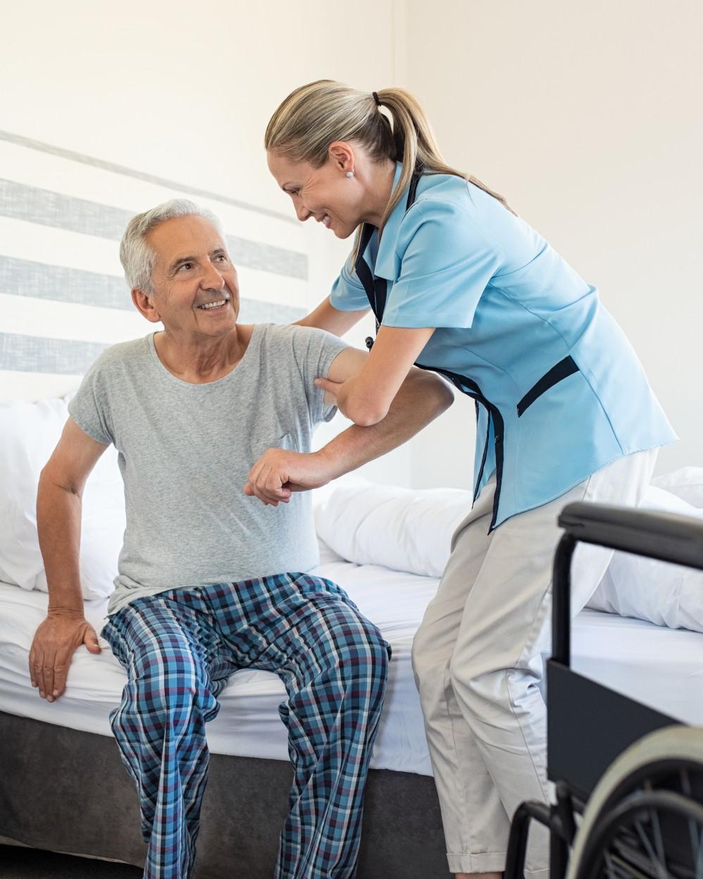 badante aiuta signore anziano ad alzarsi dal letto