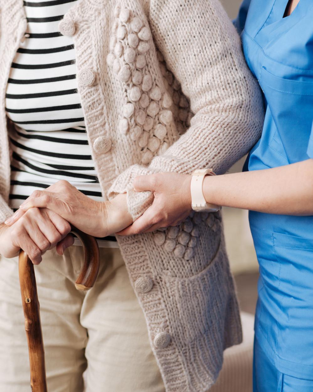 infermiera aiuta una signora anziana a caminare