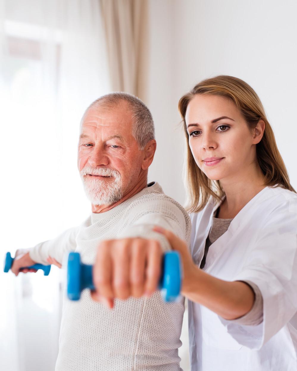 uomo anziano durante terapia occupazionale con pesi